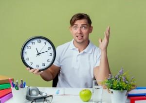 estudiante-masculino-hermoso-joven-sorprendido-que-sienta-escritorio-herramientas-escuela-que-sostienen-reloj-pared-mano-abierta-aislada-verde-oliva_141793-83930